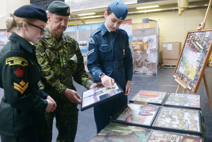 "Capt. Greg Gallant, curator of the P.E.I. Regiment Museum, Air Cadet Cpl. Harper Hippenstall, left, and Cadet Master Cpl. Sophie Flower, right, look over some of the artifacts included in the ""From Vimy to Juno"" exhibit on display at the P.E.I. Regiment Museum. The exhibit, created by the Juno Beach Association in partnership with Heritage Canada, is on display in P.E.I. until April 12."