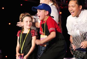 Emery Wood jumps with excitement the moment his name is announced as the winner of the first Junior Chef Challenge at the P.E.I. International Shellfish Festival. Looking on with excitement behind him is his sous-chef Mark Singson, who was the runner-up in season six of Top Chef Canada. On the left is fellow competitor Annabella Sly.