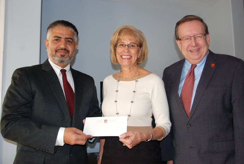 Hamad Alawadi, left, the Charges d'Affaires for the United Arab Emirates Embassy in Canada, presents a cheque for $20,000 US to Stars for Life Foundation for Autism president Carolyn Bateman as P.E.I. Senator Percy Downe looks on. Downe was instrumental in securing the donation for the Island not-for-profit organization.