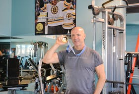 Dave (Eli) MacEachern shows off the gold medal he won at the 1998 Nagano Olympics for the two-man bobsleigh event at Dynamic Fitness in Charlottetown on Feb. 17.