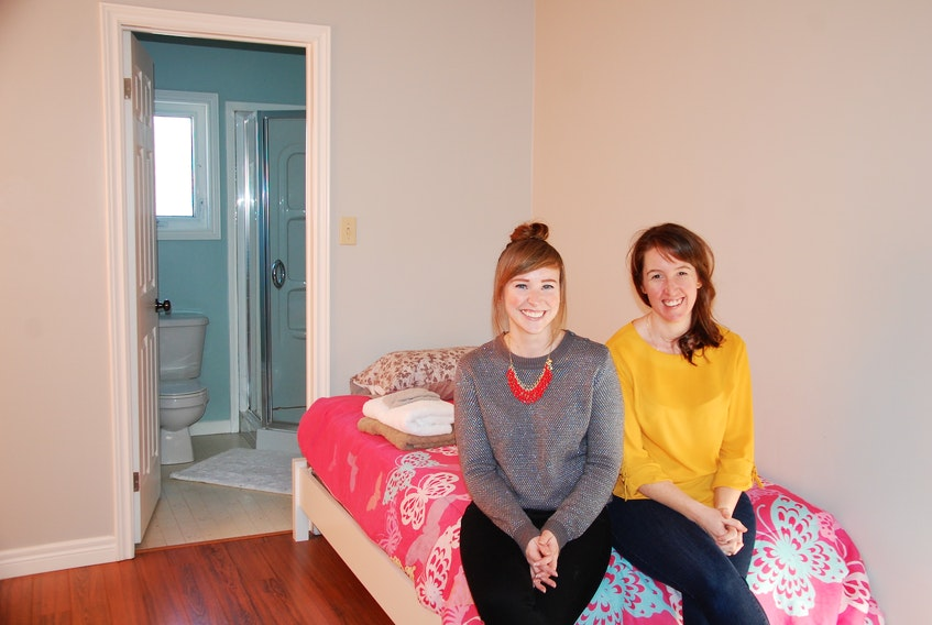 Blooming House co-founders Liz Corney, left, and Brynn Devine sit on a bed in one of the bedrooms in the new shelter for women that opened Friday, Jan. 25, 2019.