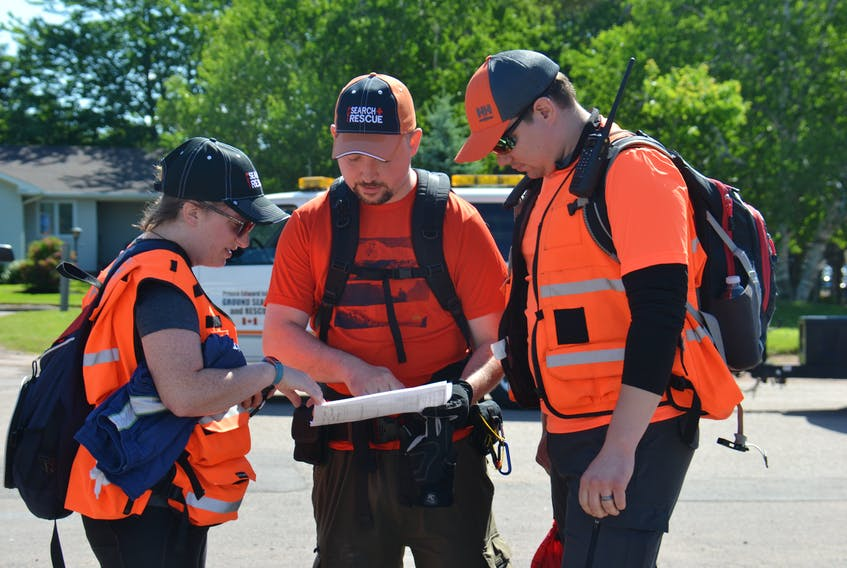 Volunteers with P.E.I. Ground Search and Rescue go over their instructions for a mock search and rescue held in Montague and Brudenell on Sunday.