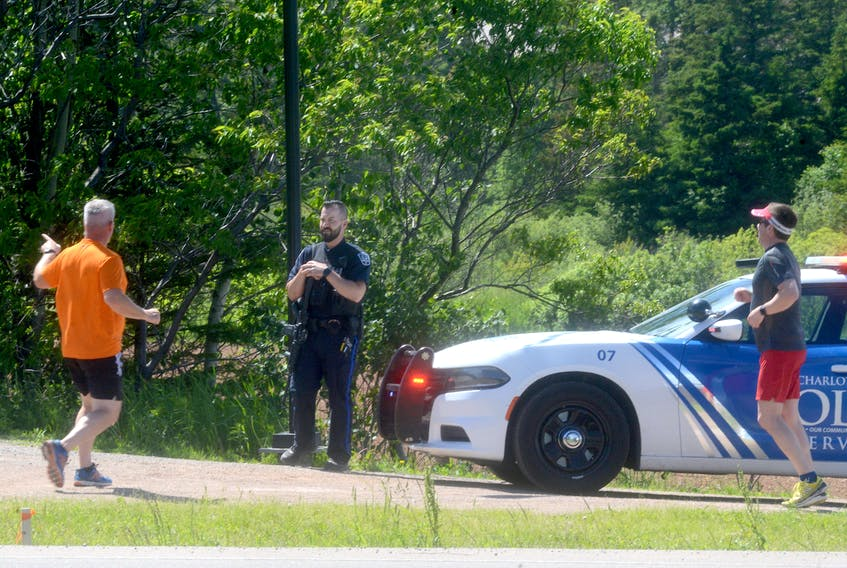 A Charlottetown police officer with a carbine rifle advises two joggers Monday afternoon of a closure at the Confederation Trail. Police blocked off a section of the trail near the bypass highway after hearing a report of a man with a firearm.