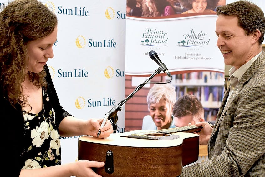 Catherine MacLellan donated one of her guitars to the Summerside Rotary Library Thursday morning. MacLellan performed as part of a presentation dozens of musical instruments and $140,000 to maintain them and from Sun Life. The instruments are now part of the provincial collection and anyone with a library card can borrow one. The library is also accepting instrument donations from the public, like the guitar from MacLellan. The money from Sun Life will allow the library to get donated items checked over and made ready for lending. MacLellan (pictured) signed her guitar for Education Minister Brad Trivers at the Summerside Rotary Library June 6.