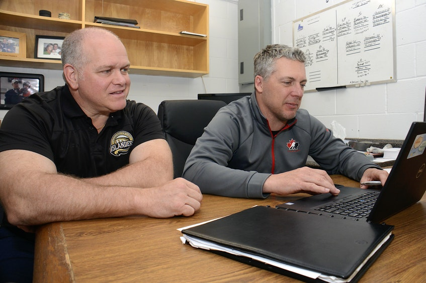 Charlottetown Islanders assistant general manager Guy Girouard, left, and general manager Jim Hulton go over various draft scenarios in advance of the 2016 Quebec Major Junior Hockey League draft in Charlottetown. - Jason Malloy