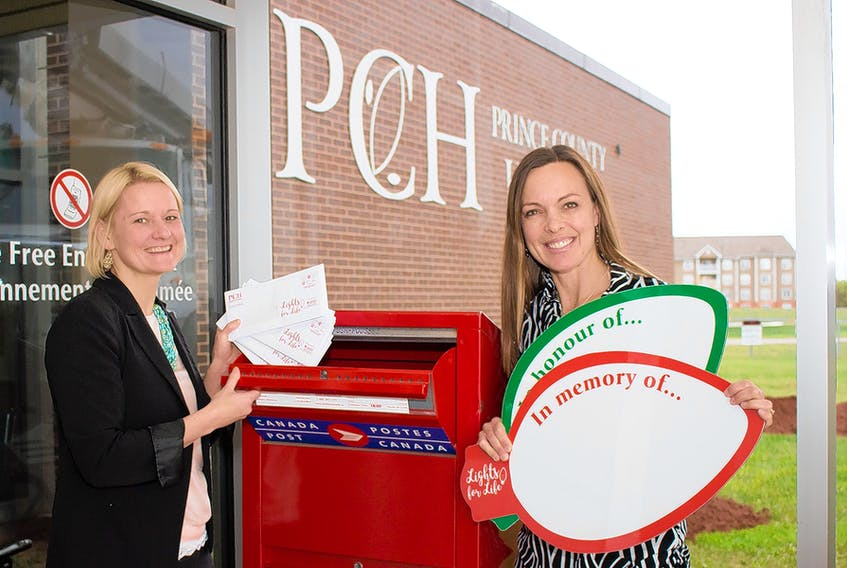 Sandra Zarvie, left, and Lisa Schurman-Smith, of the PCH Foundation staff get prepared for Lights for Life. Packages like the ones Zarvie is holding are in mailboxes now. Gifts can also be made online at pchcare.com or in the PCH Foundation office in the hospital lobby. The foundation office also has the special bulbs Schurman is holding to take commemorative photos so people can share memories through Lights for Life on social media. Submitted photo/Bevan Woodacre