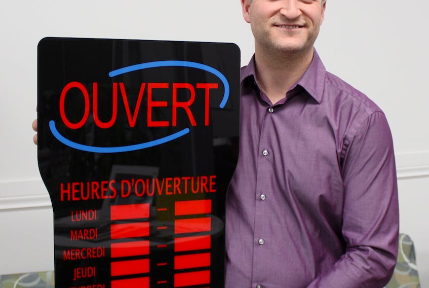 Pierre Gallant, owner of HMS Office Solutions in Summerside, shows one of the LED signs he sells to help francophone and bilingual businesses show visitors they offer services in French. Submitted photo