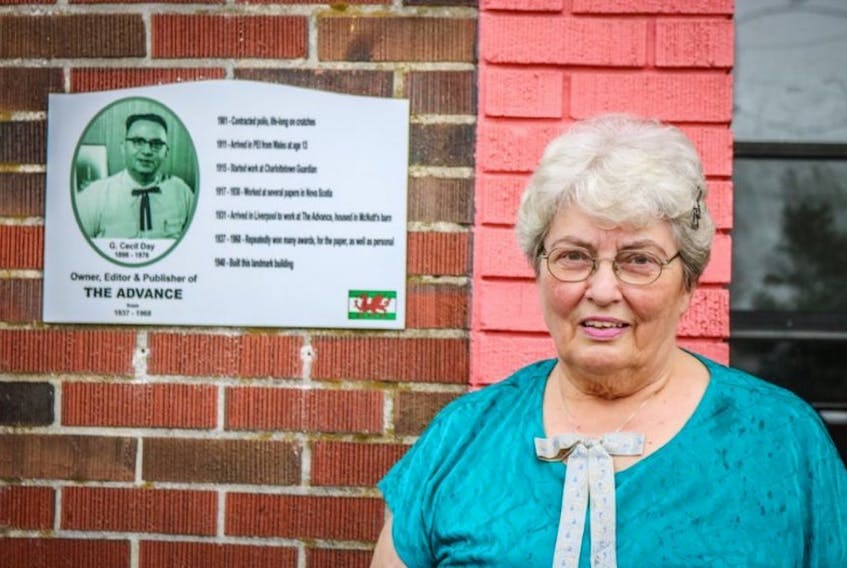 Beverley Day Burlock stands next to a plaque on the Queens County Advance Building in Liverpool that honours her father, G. Cecil Day. Day, who is a former editor at The Guardian, will be inducted into Atlantic Journalism Hall of Fame today during a ceremony in Halifax.