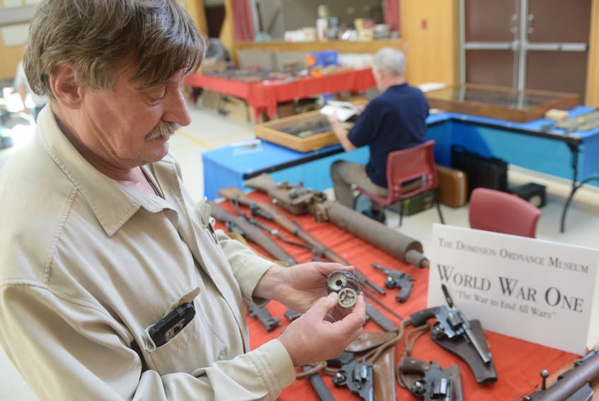 Steve Knechtel, president of Belle River's Dominion Ordnance Museum, looks at a British grenade next to the museum's display of First World War firearms and ammunition during this year's P.E.I. Gun and Memorabilia show in the North Shore Community Centre. (MITCH MACDONALD/THE GUARDIAN)