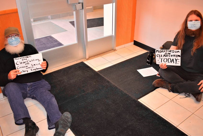 As part of the clearcutting sit-ins, Paul Jenkinson (left) and Tristan Smith sit in the entrance way to the Department of Lands and Forest office in downtown Truro.