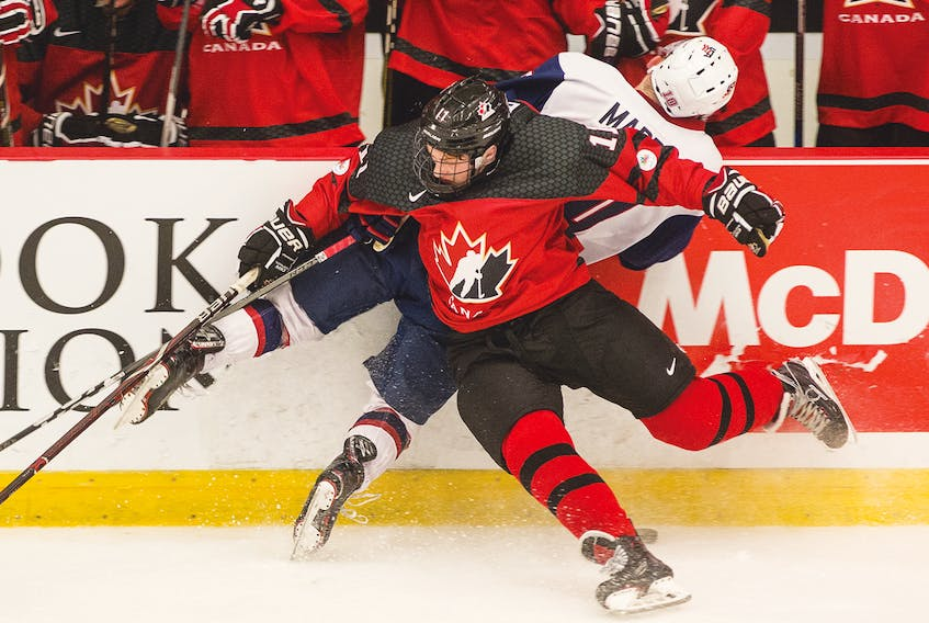Canada West's Brendan Budy stuffs USA's Tyler Maden into the boards in front of the Canada West bench during World Junior A Challenge action on Tuesday in Truro.
