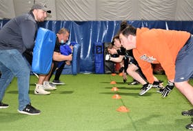 Canaan Hebb (right) starts to explode out of his stance in a lineman drill during the recent football camp held at the Cougar Dome. The former CEC player said he appreciated the many experienced coaches who were on-hand to pass along their knowledge.
