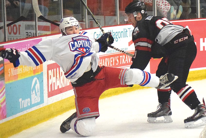 Jordan Spence of the Summerside Western Capitals goes flying after a check from Dylan Burton of the Bearcats during MHL action Friday in Truro.