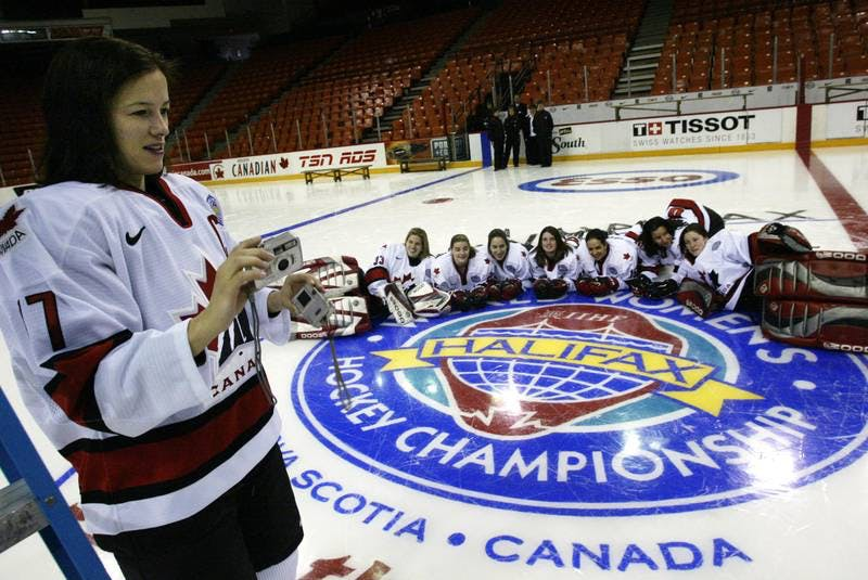 Team Canada captain Cassie Campbell is seen checking her camera while photographing teammates posing on the 2004 world women's hockey championship logo following their team picture at the Halifax Metro Centre. - SaltWire Network