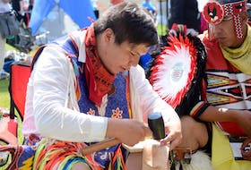 Paskwa Lightning, left, from Maskwacis in Alberta painstakingly fastened together a leather belt at the Millbrook First Nation Competition Powwow on Aug. 10 as his friend Stephane Mapachee from Pikogan, Quebec, looked on. Lightning says the finished belt will sell for about $400.