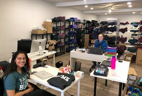"""My Home Apparel employees Amy Allain, Shekara Grant and Maddie Richards are seen working on the new """"Stay the blazes home"""" T-shirts that are being sold as a charitable fundraiser."""