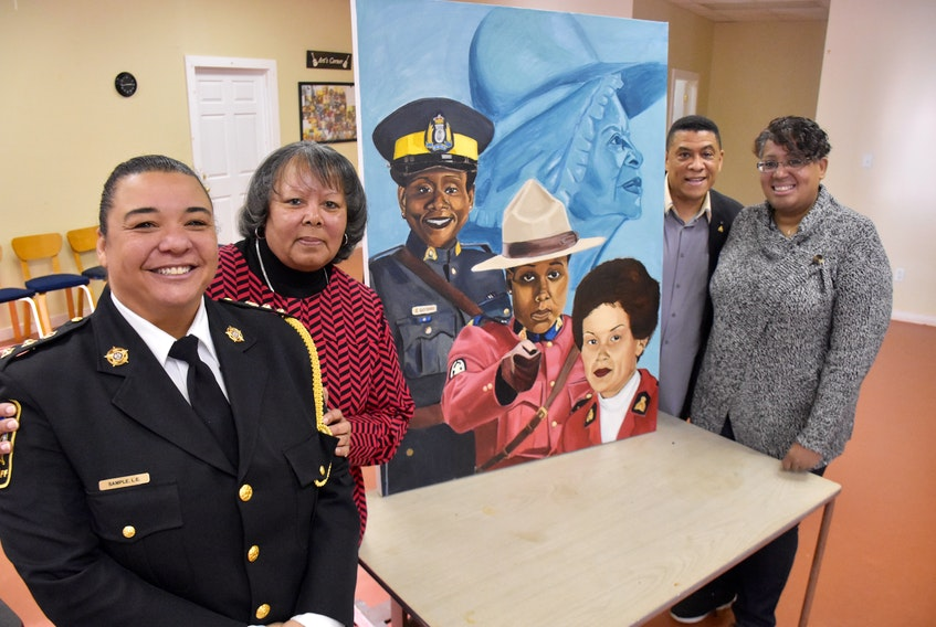 Leanne (MacDonald) Sample, Cathy Thomas, Sgt. Craig Smith and Carmelita (Cromwell) Johnson stand next to a painting by Letitia Fraser that features images of Rose Fortune, Insp. Sherley Goodgie, Const. Carline‎ Fidele and Const. Shelley Peters during an event in Yarmouth County celebrating 'Black Women Making a Difference in Canadian Law Enforcement.' TINA COMEAU PHOTO