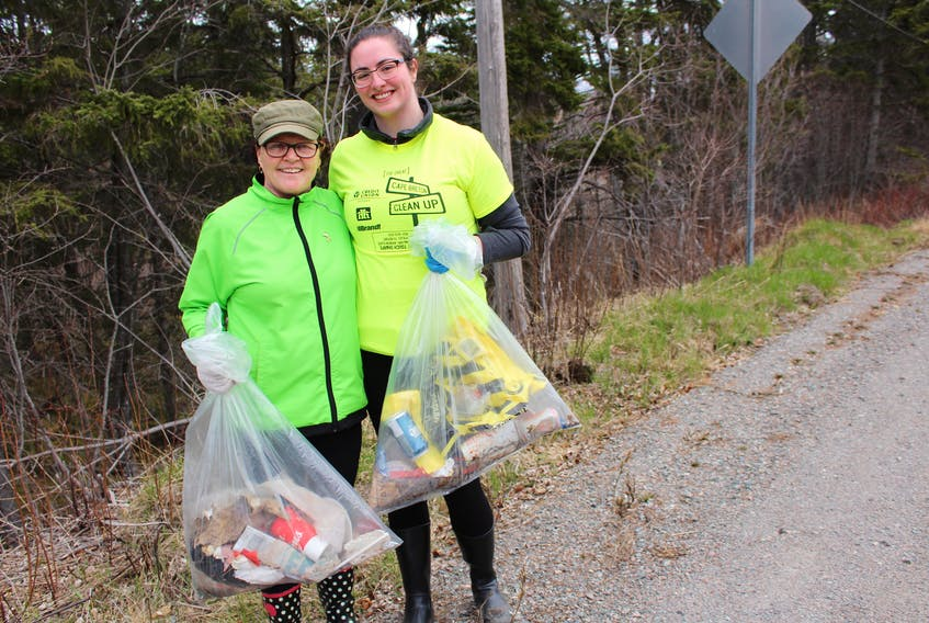 Helping clean up the streets of Balls Creek along Frenchvale Road on Saturday was Donna Deleskie, left, and Mairi-Jo Musgrave. Food and beverage containers were among the items found.