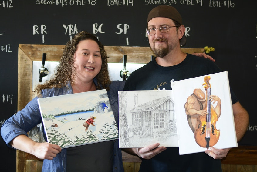 Trider's Craft Beer co-owner Laura Parker and her brother-in-law Ken Potter work together to create the fun, unconventional labels found at Trider's Craft Beer. She pitches concepts to him and he brings them to life through his drawings. Laura is holding Ken's painting for the Hibrrrnation Winter Ale, and Ken is holding his drawings for the Maccan Maple and Mean Joe Bean beers. The shed depicted in the Maccan Maple label is located on Trider Road in Maccan where Trider's began brewing beer before moving to their current facility in Amherst.