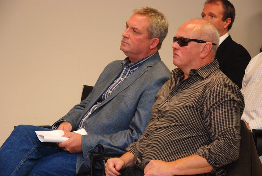 Fisheries and Land Resources Minister Gerry Byrne (left) and Terry Gardner listen to a speaker during Friday's news conference in Corner Brook. The minister announced changes to provincial wildlife regulations.