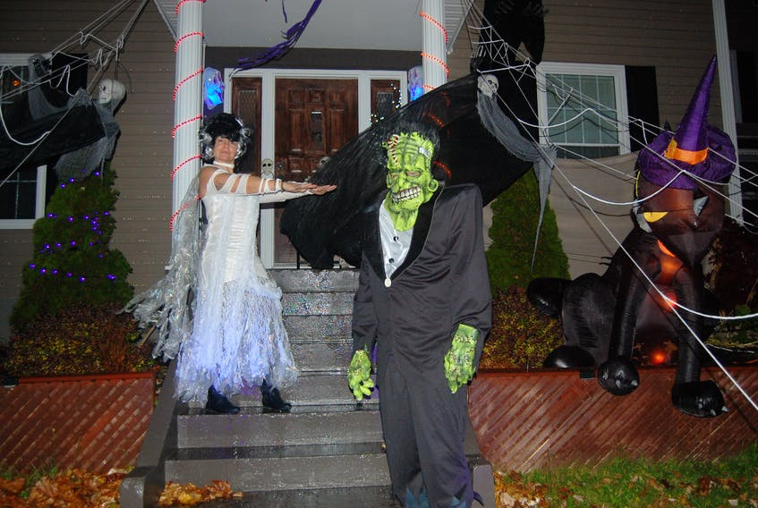 """Susan and Sheldon Lane love the Halloween season. They are seen here in costume as """"Bride of Frankenstein"""" and """"Big Frankie"""" in front of their decorated home at 23 Hillview Avenue in Stephenville."""