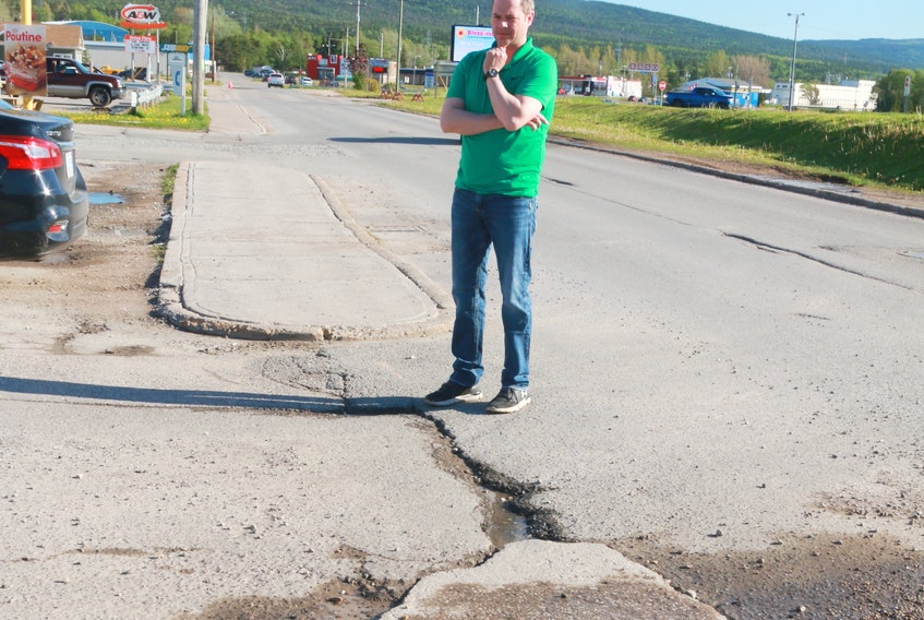 Deer Lake's Mike Goosney stands next to one the three potholes he helped fix in the community last year.