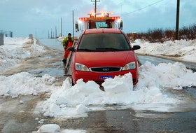 Dave Slade of Eddy Services Towing and Transport works at removing a car from a snow bank on Massachusetts Drive in Stephenville, one of two vehicles that got stuck in the location during Thursday night's storm.