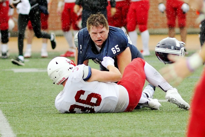 St. F.X. X-Men offensive lineman Gregor MacKellar loses his helmet in this battle with his Acadia opponent during an exhibition contest, Aug. 18, at Oland Stadium. Bryan Kennedy