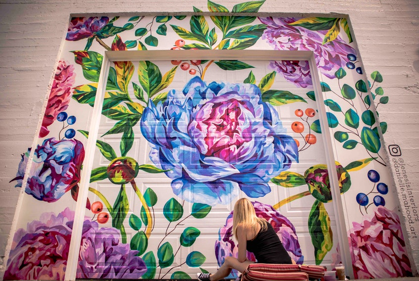 Danielle Mahood at work on the mural commissioned in 2019 by Jenesis Interiors on Water Street.  Keane Wheeler Photo