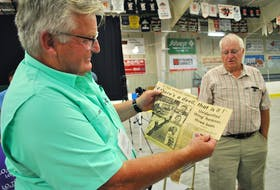 Cape Sable Island fisherman Rodney Ross holds up a clipping from the a July 1976 Yarmouth Vanguard issue that chronicled the story of the encounter by five fishermen aboard three fishing boats with a mysterious sea creature.  KATHY JOHNSON PHOTO
