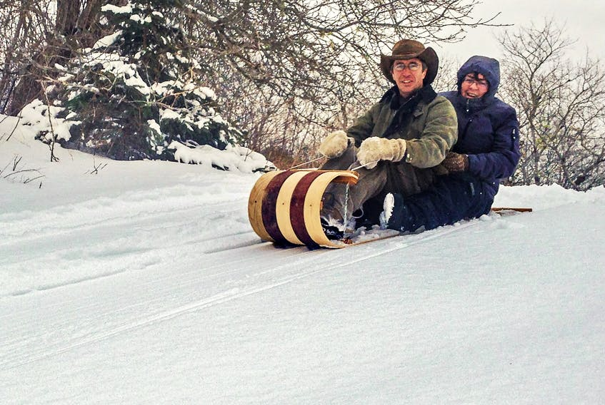 Dan Peacock and his wife Dorothy enjoy some winter fun on one of his handmade toboggans.