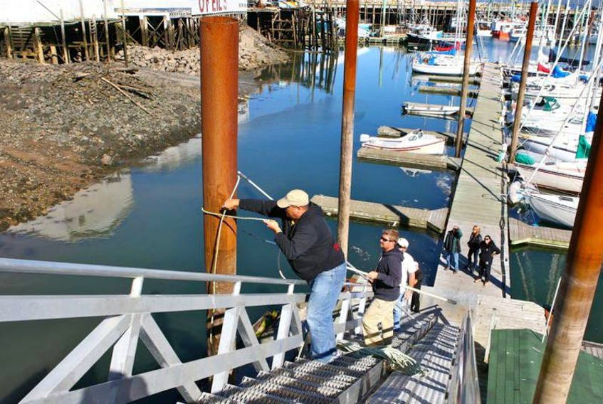 Boat owners Mike Carter, top, and Colin Bondy lash a steel support pylon, hoping to guide its swaying in this file photo from last September at the Digby Yacht Club. FILE PHOTO