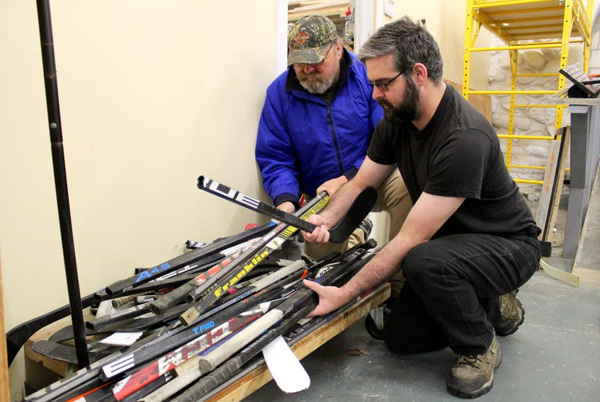 Kevin Ellis (left) and Stephen Davidson sort through some old hockey sticks. The two are among those working on the hockey furniture project at The Store Next Door in Yarmouth.