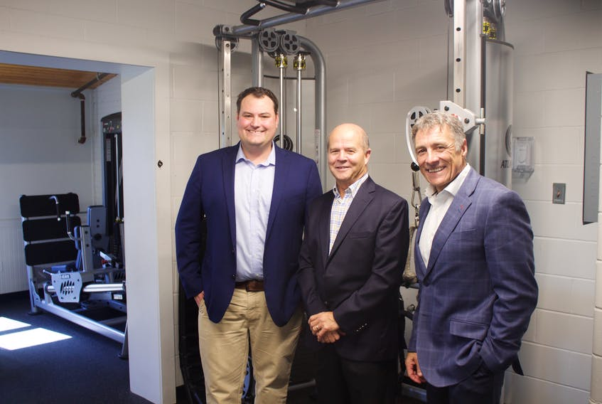 Colin Fraser, Member of Parliament for West Nova, Noel Despres, CEO and President of Comeau's Seafood and Allister Surette, President of Université Sainte-Anne, in the newly renovated weight room, part of the renamed Marcel R. Comeau Sports Centre.