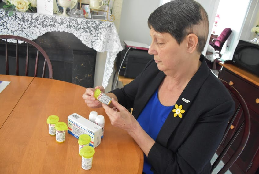 Sandy Dennis looks over some of the pills that she has to take on a daily basis because of her cancer TINA COMEAU PHOTO