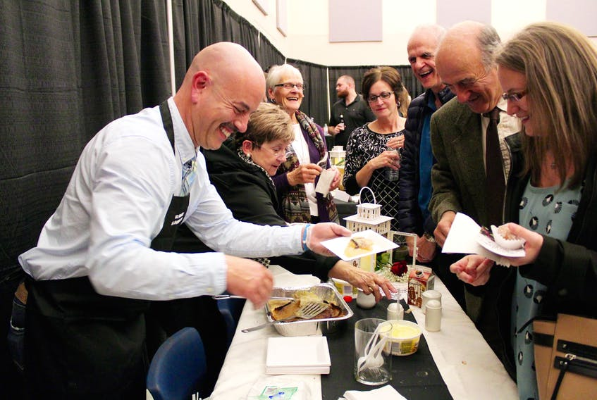 Greg Pottier (left) of Carl's Store serves up some rappie pie during the Taste of Argyle event Nov. 16 in Tusket, part of an evening billed as Experience of Argyle. ERIC BOURQUE PHOTO