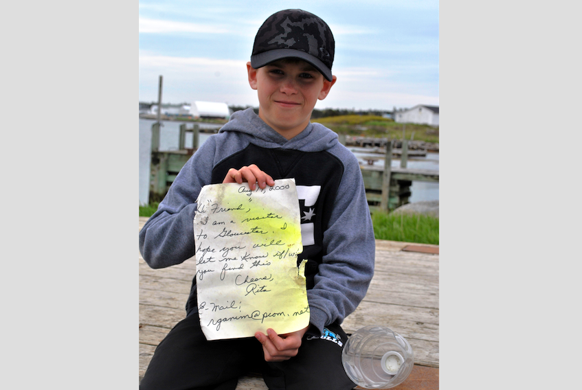 Dallas Goreham holds up the note he found in a bottle on May 16 washed up on the Lower Woods Harbour shoreline, 18 years after it had been tossed into the ocean in the waters off Gloucester, Massachusetts.