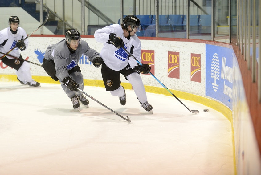 Defenceman Lukas Cormier cycles the puck to a teammate while being defended by Drew Elliott at Monday's Charlottetown Islanders practice at the Eastlink Centre.