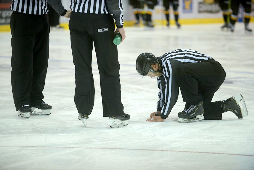 Linesman Tanner Doiron tries to repair a hole in the ice during Tuesday's Quebec Major Junior Hockey League game at the Eastlink Centre.