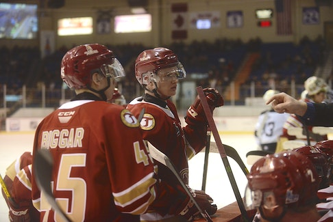 Zach Biggar, left, and Cole Larkin listen to a coach during a game at the Eastlink Centre in the 2019-20 Quebec Major Junior Hockey League season.