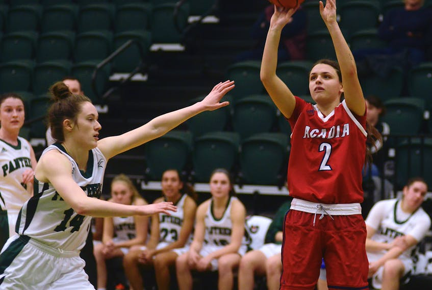 Acadia Axewomen guard Haley McDonald, right, takes a shot over UPEI's Annabelle Charron during the first half of Saturday's game in Charlottetown.