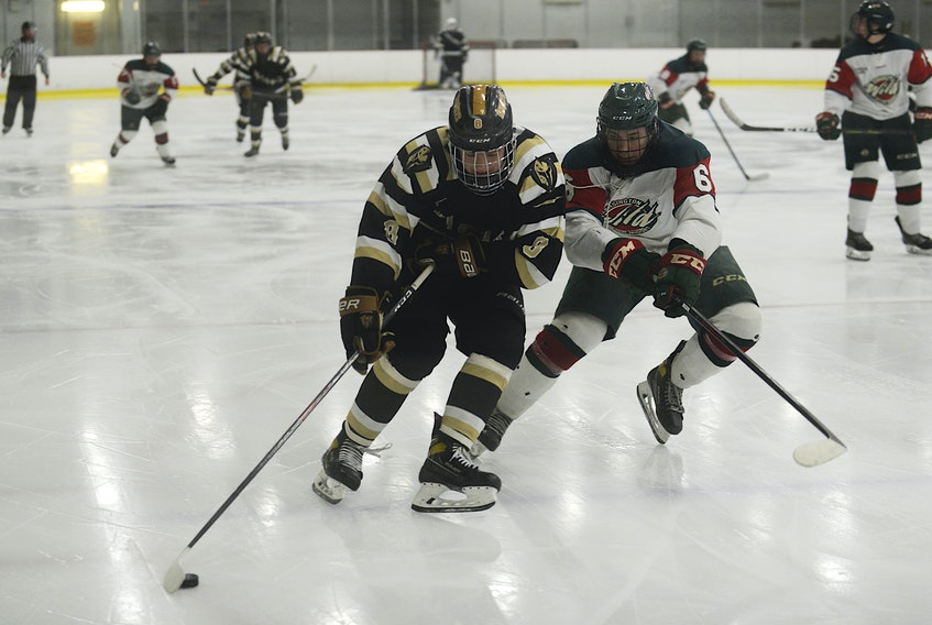 Charlottetown Bulk Carriers Knights forward Jude Campbell, left, tries to drive around Kensington Monaghan Farms Wild defenceman Kieran Rennie during Friday's Game 3 of the P.E.I. major under-18 hockey championship at MacLauchlan Arena in Charlottetown.