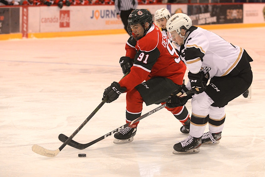 Halifax Mooseheads forward Elliot Desnoyers, left, and Charlottetown Islanders defenceman Braeden Virtue battle for the puck Wednesday during Quebec Major Junior Hockey League action in Charlottetown.