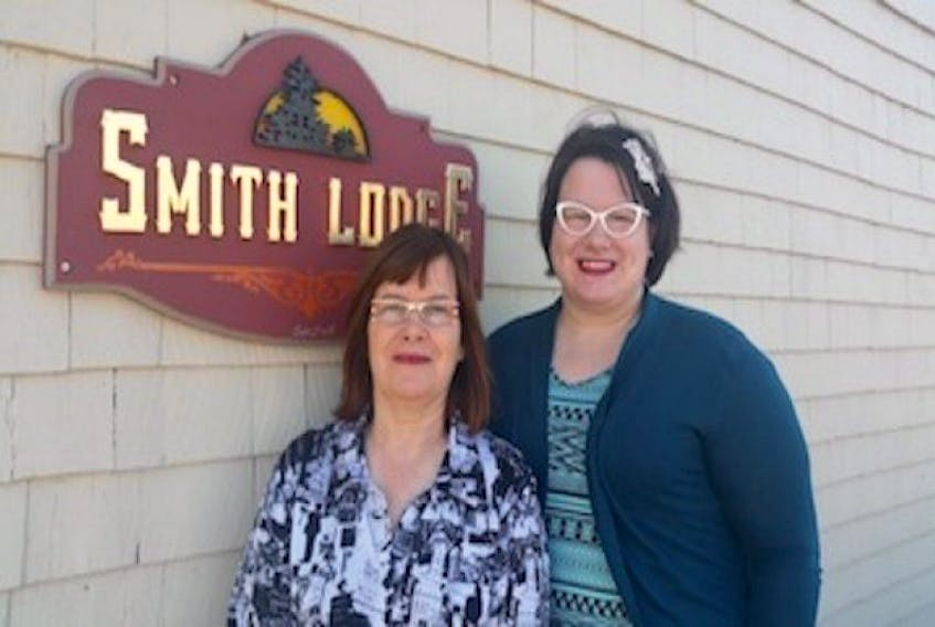 Dianne C. Smith, left, and her daughter, Leone Dixon, stand at the entrance of Smith's Lodge in Charlottetown. In a commitment to making her life better for her and her family, Smith started the business after getting her GED and taking the Red Cross home care program.