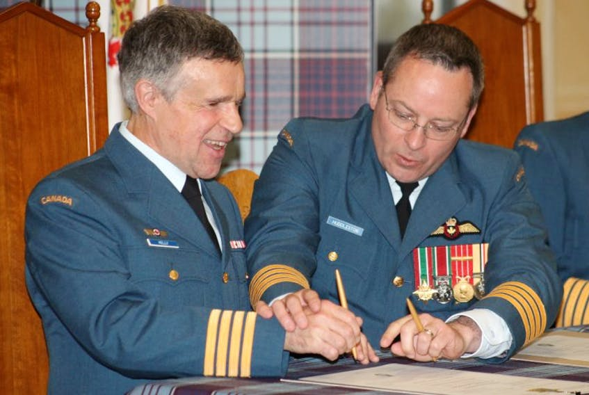 Wing Commander Col. Iain Huddleston, right, assists Terry Kelly in signing the documents investing him to the position of Honorary Colonel of 14 Wing Greenwood. The well-known Atlantic Canadian musician and inspirational speaker was invested at a July 6 ceremony at the Wing.