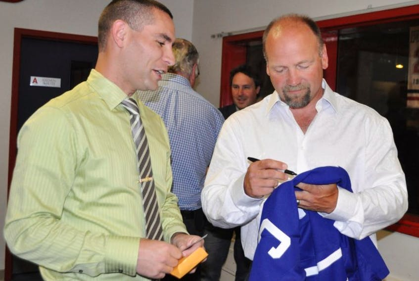 Wendel Clark autographs a sweater for a fan during a pre-dinner reception in the Hall of Fame Room at Acadia Arena