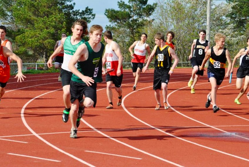 <p>Lukas Kane hands the baton to Central Kings teammate Kurt Getson during the boys' 4X100 relay at the 2013 Acadia Relays meet May 10 in Wolfville.</p>