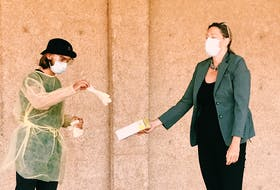 Acadia Students' Union president Brendan MacNeil prepares to conduct a COVID-19 nasal swab on researcher Dr. Lisa Barrett. CONTRIBUTED