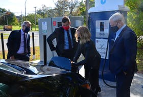Acadia University Community Development professor Dr. Gabrielle Donnelly demonstrates how to charge her electric Nissan Leaf for Acadia president Dr. Peter Ricketts, Kings-Hants MP Kody Blois and Kings South MLA Keith Irving. KIRK STARRATT