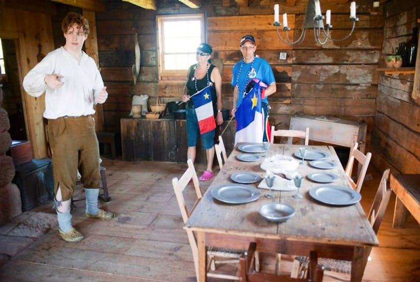 Malachi Rosewell, interpretor at the Doucet House in Rustico, gives the history of the building to Mario Cormier and Debbie Cormier during National acadian day celebrations Saturday.